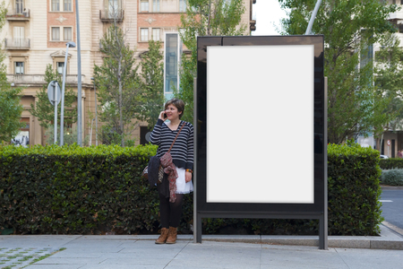 sidewalk talk: Woman talking with mobile phone, standing in a blank billboard