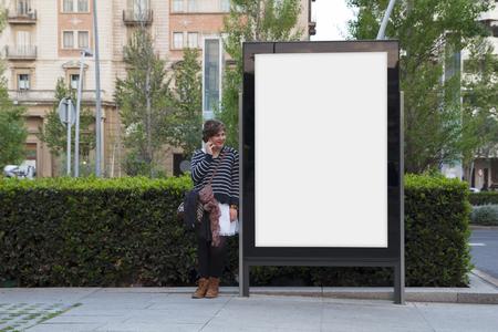 sidewalk talk: Woman talking with mobile phone, standing in a blank billboard