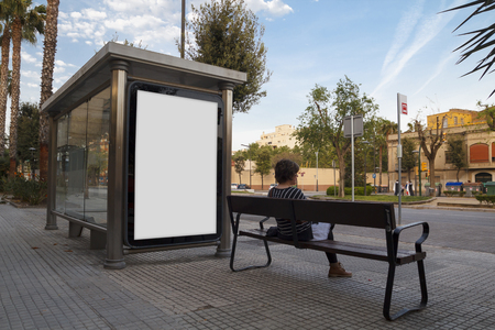Le billard blanc se moque dans un arrêt de bus, avec une jeune femme assise dans un banc