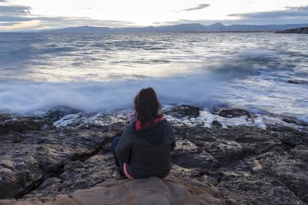 Femme seule assise à côté de la mer, dans une longue exposition