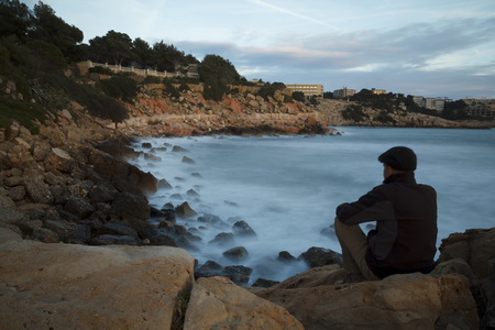 Homme seul assis à côté de la mer, dans une longue exposition