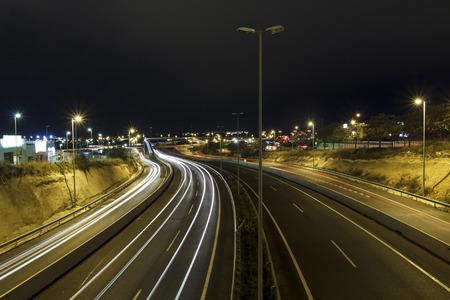 Prise d'exposition prolongée de l'autoroute la nuit, avec les voitures conduisant dans la route Banque d'images