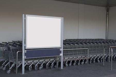 billboard Blank dans un supermarché, à côté des chariots