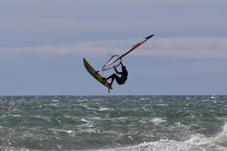 Windsurf acrobatic jump in the sea