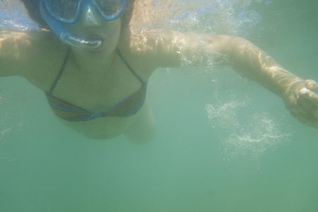 Woman swimming underwater, with snorkel mask and pipe Banque d'images