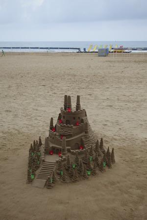 Château de sable à la plage avec des bougies colorées