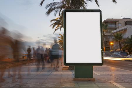 Panneau d'affichage en blanc dans un sentier au coucher du soleil, avec des gens en flou marche Banque d'images