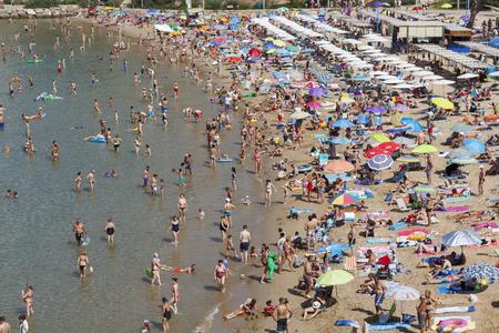 Plage bondée à l'été, avec beaucoup de gens s'amuser