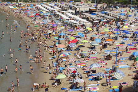 SALOU, SPAIN - AUGUST 03, 2017: People relaxing and having fun on the beach to have their holidays at the coast of Salou, Spain, a famous tourist destination