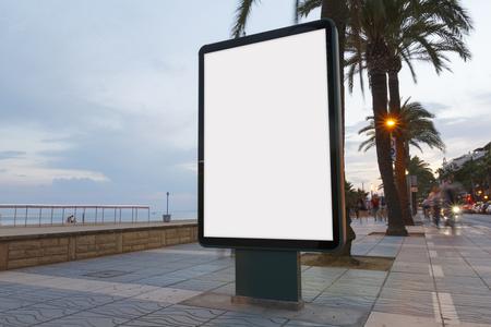 Panneau d'affichage en blanc dans un sentier, à côté de la mer