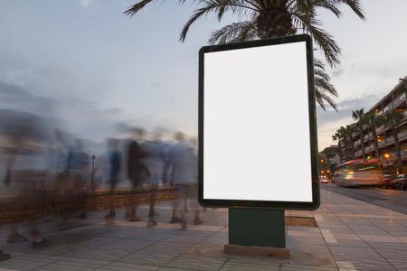 Blank billboard in a footpath at sunset, with blurred people walking Banque d'images