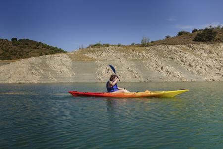 Jeune femme avec un kayak coloré dans un lac
