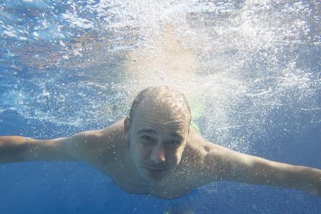 Homme nageant sous l'eau face à la caméra