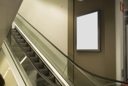 Blank billboard in a shopping mall, next to mechanical escalator