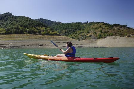 Jeune femme avec un kayak coloré en été
