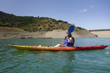 Young woman with a colorful kayak in a dam