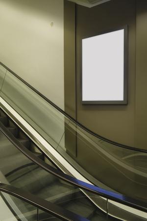 Panneau d'affichage vide dans un centre commercial, à côté de l'escalator mécanique