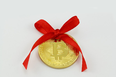 Golden bitcoin with a red ribbon, valuable gift