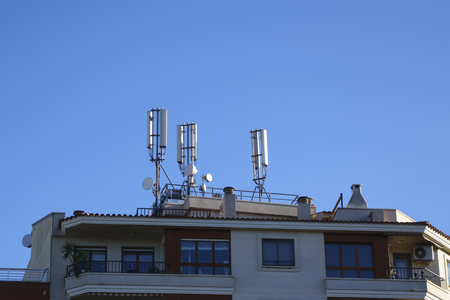 Mobile antenna in the roof of a building, against blue sky Banque d'images
