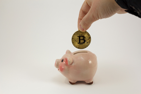 Human hand throwing a bit coin in a pig piggy box