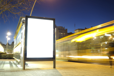 Blank advertisement mock up in a bus stop, with blurred traffic lights at night