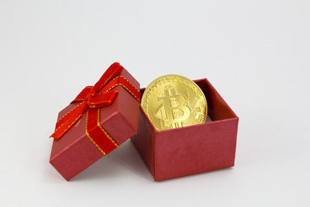 Bitcoin golden coin in a red gift box, isolated in a white background Banque d'images