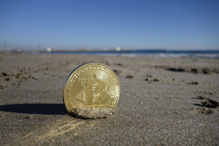 Golden bitcoin currency at the beach Banque d'images