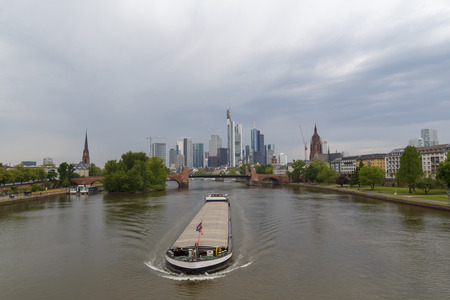 Frankfurt city view from river Main, with sailing cargo ship