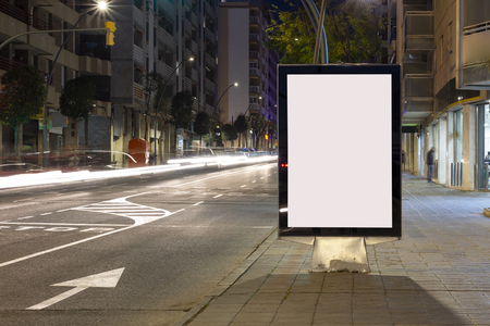 Blank advertisement billboard, with blurred traffic lights at night