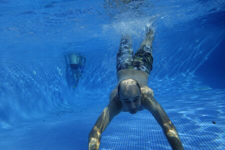 Man swimming underwater in a swimming pool, facing the cam