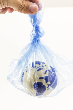 Human hand holding an earth globe inside a plastic bag, pollution and warming concept Stock fotó