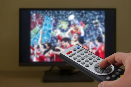 Football match winner team celebrating with the cup in television, with a remote control in the hand Stock Photo