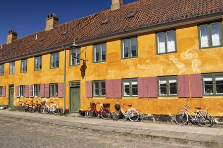 Historic row yellow houses in Nyboder neighborhood in Copenhagen, a former Naval district with bikes in front of the houses