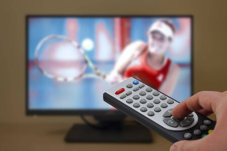 Watching a tennis match in the television, with a tv remote control in the hand Stock Photo