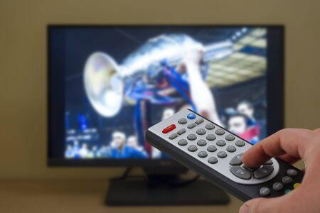 Fußballspiel-Siegerteam feiert mit dem Pokal im Fernsehen, mit einer Fernbedienung in der Hand