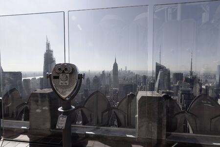 Top of the Rock lookout at Rockefeller center in New York, with binoculars focused to Empire State building in Manhattan Banque d'images