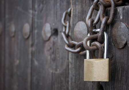 forefront of a padlock closing an old wooden door