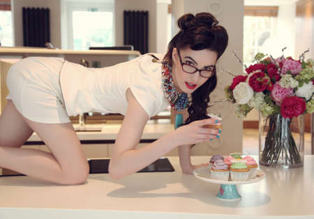 50s pinup girl tasting cupcakes photo