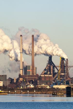 Hoogovens met rokende schoorstenen in IJmuiden; Blast furnaces with smoking chimneys at IJmuiden Redactioneel