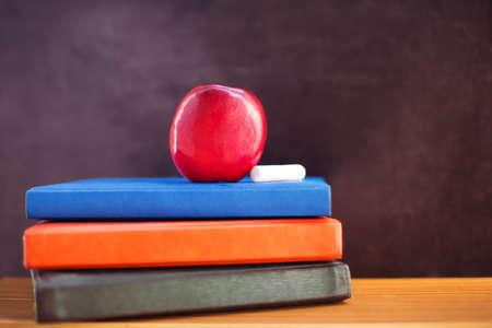 Red apple and chalk lying on books near blackboard photo