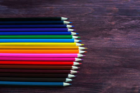 colored pencil: coloured pencils in a row on dark background Stock Photo