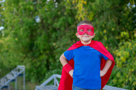 Boy dressed in cape and mask standing with hands on hips and smiling