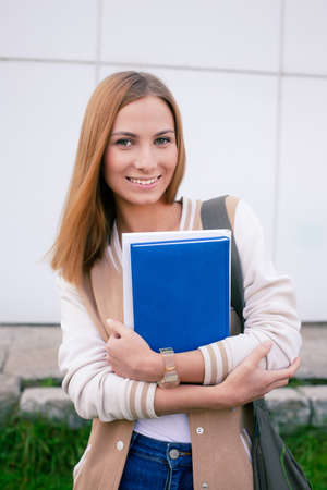 16 17 years: Student standing with books in her hands and smiling at camera Stock Photo