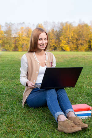 16 17 years: Student sitting with a laptop and books on the grass