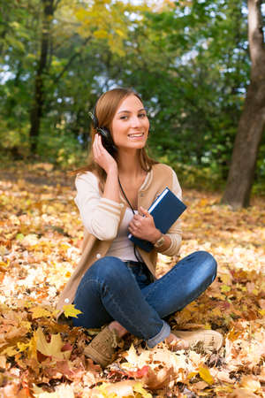 16 17 years: Student sitting with headphones among maple leaves Stock Photo