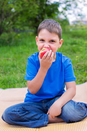 beach mat: Boy eating red apple and sitting on beach mat