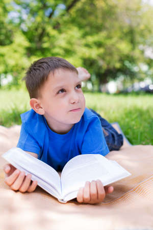 Boy lying on picnic and dreaming under book. Selective focus photo