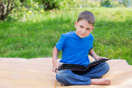 beach mat: Boy sitting with opened album on beach mat Stock Photo