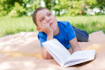 Boy dreaming under book with humour. Selective focus photo