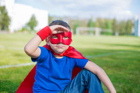 invincible: Boy dressed in cape and mask sitting and looking from under his hand